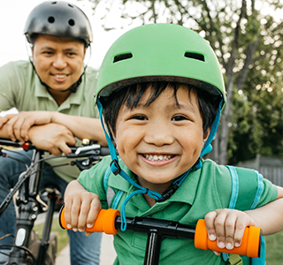 Child on bike smiling with Dad following behind