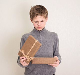 Kid opening present box and frowning