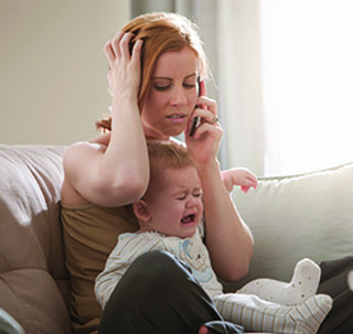 Mom on the phone frustrated while baby is crying
