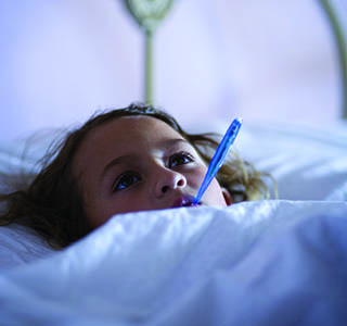 Girl in bed with thermometer