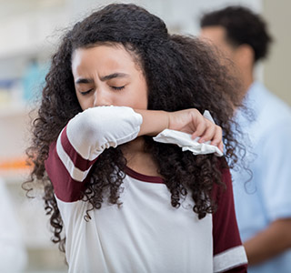 Girl sneezing into elbow