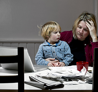 Frustrated mom at table looking at papers