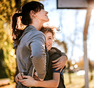 Mom hugs her preteen son. They are wearing sports clothes and near a basketball goal outside on a sunny day.