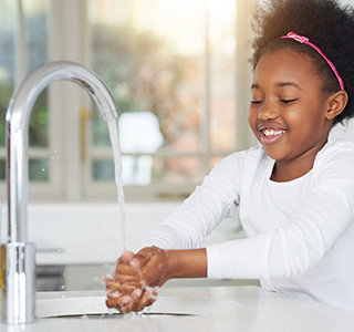 child washing hands at sink
