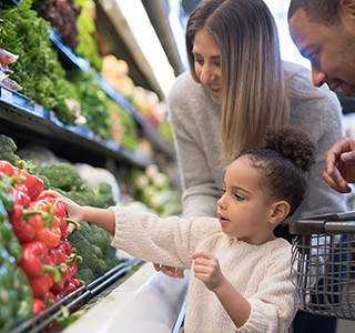 Young child reaching for red bell pepper in grocery store with parents behind her.