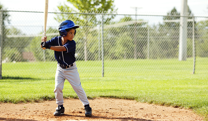 Young boy wears blue baseball uniform and holds bat over the plate while looking at the mound.