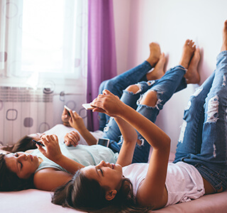 teenage girls lounging and playing on phone