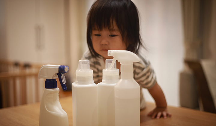 Toddler girl wearing a grey striped shirt leans over a table to look at four white cleaning products.