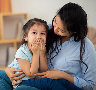 Child covering her mouth while mom looks at her - Parent-ish parenting blog