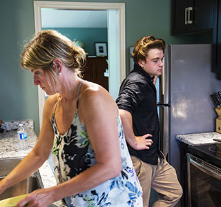 Teen and mom in kitchen cleaning