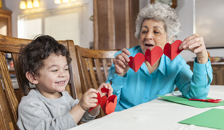 Young boy and grandma cutting heart paper garlands