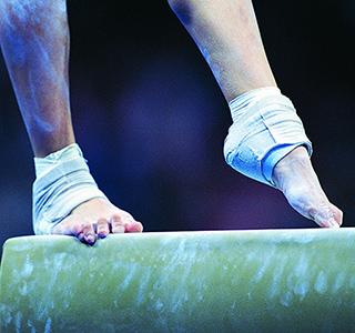 Woman's feet on gymnastic balance beam