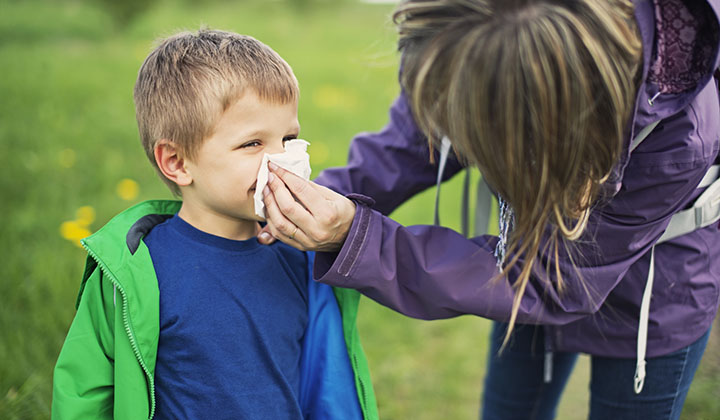 Mom using tissue on son's nose