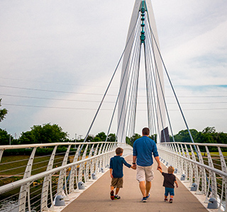Brandon Billinger holds hands with his two young sons walking away as the cross a walking bridge on a sunny day.