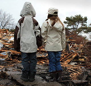 Two young children with backs to camera, hold hands and look at home debris after a storm.