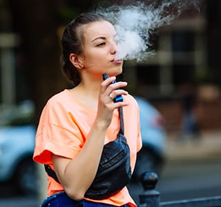 Young girl vaping outside
