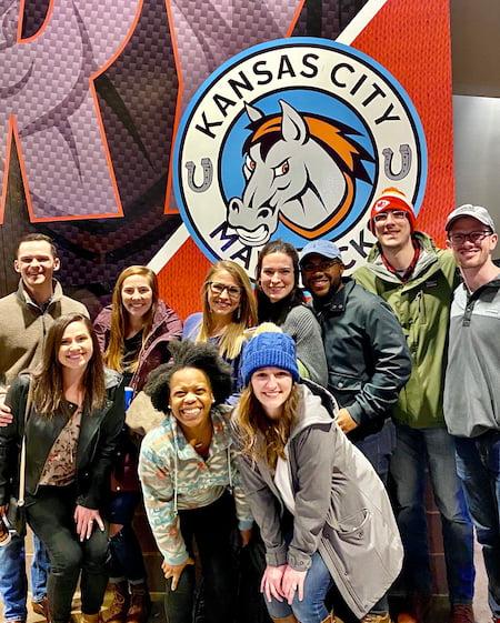 Children's Mercy Pediatric Residents pose together in front of the Kansas City Mavericks logo.
