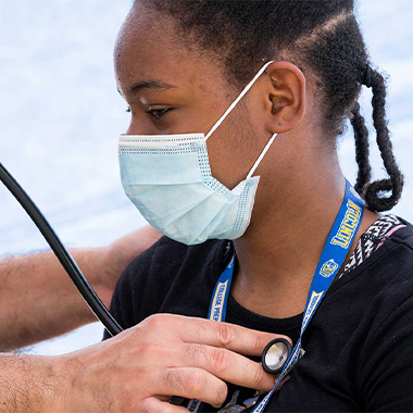 Girl in face mask with a provider pressing a stethoscope against her chest