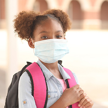 Girl with face mask wearing a backpack