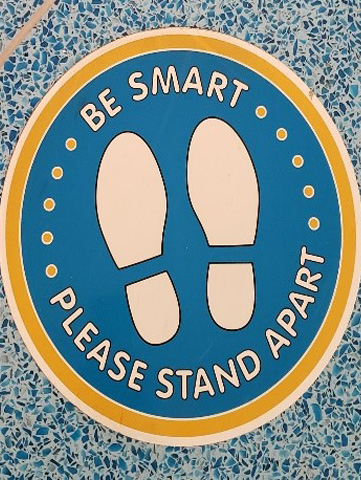 "Floor sticker that reads ""Be Smart Please Stand Apart"""
