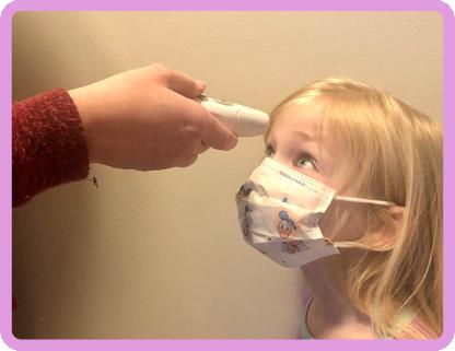 Girl in face mask having her temperature taken