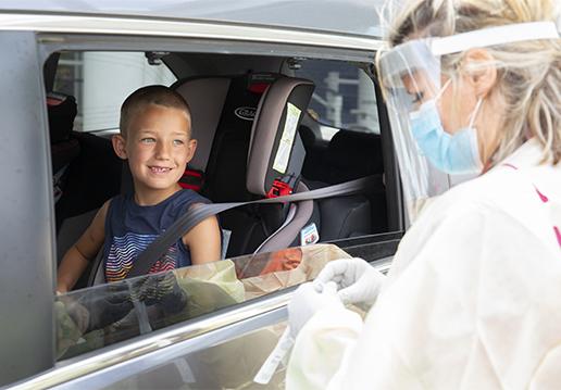 Nurse in PPE greeting boy in a car