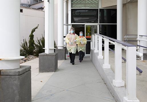 Two nurses in PPE walking from building