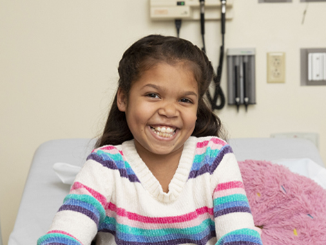 Girl smiling on hospital bed