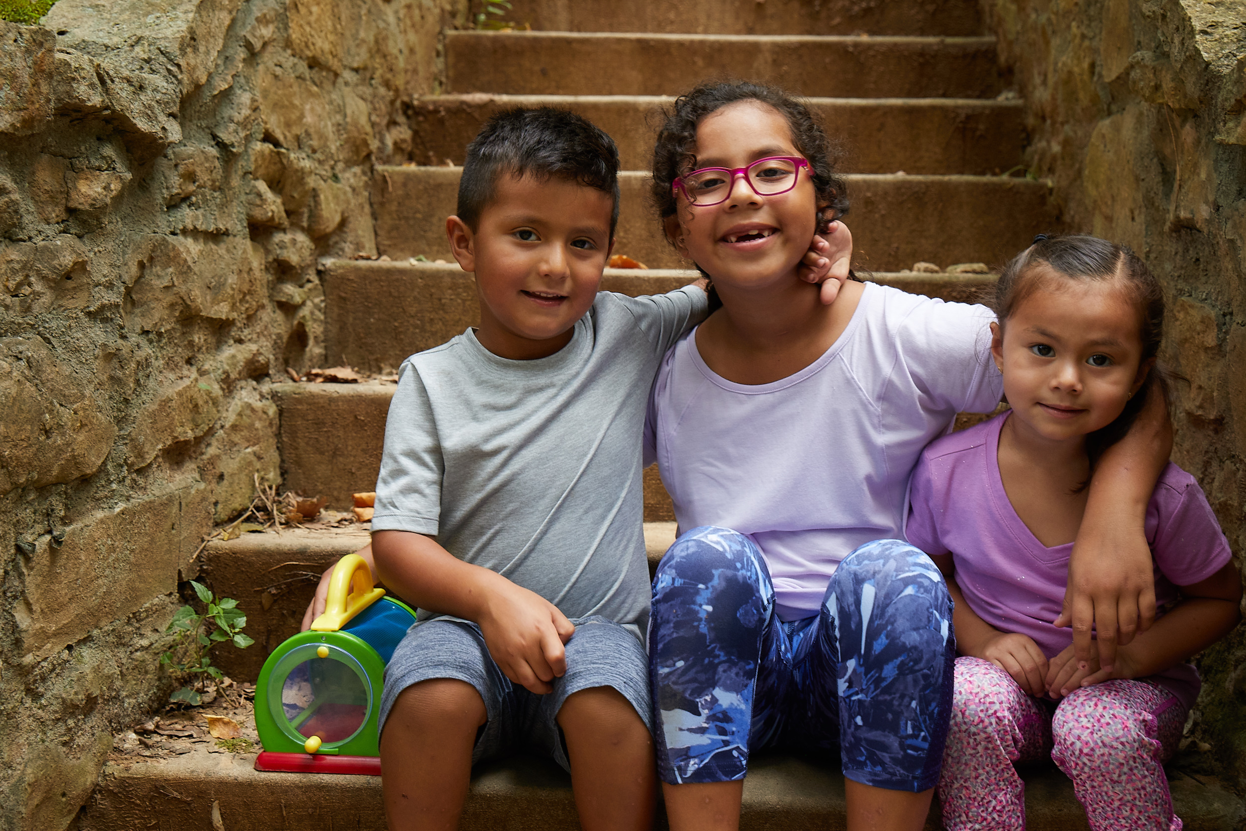 Natalia smiling and sitting with her siblings on stone steps
